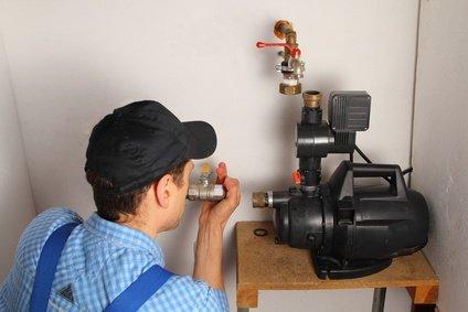 Mann schließt eine Hauswasserpumpe an | Quelle: Fotolia.com