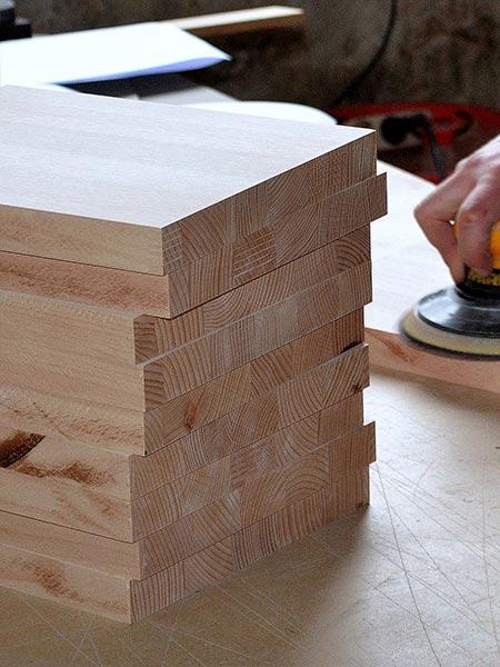 Hier sieht man einen Stapel Holzbretter vor dem Bearbeiten mit einer Flachdübelffräse oder Lamellofräse